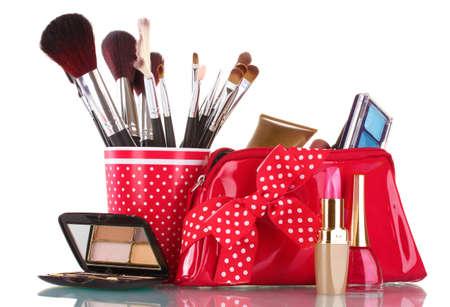 stage makeup: vetro rosso con pennelli e borsa trucco con cosmetici isolato su bianco