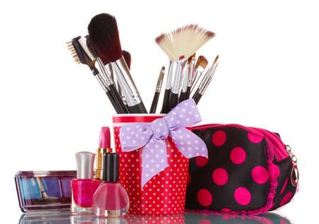 red glass with brushes and makeup bag with cosmetics isolated on white photo