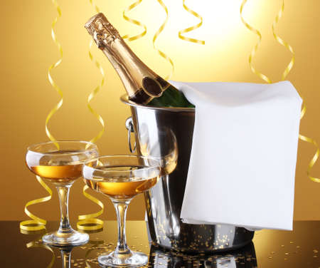 Champagne bottle in bucket with ice and glasses of champagne, on yellow background Stock Photo - 13245382