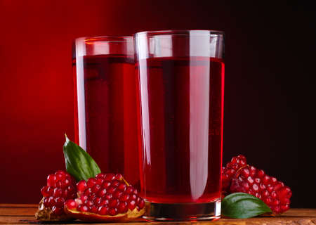 ripe pomergranate and glasses of juice on wooden table on red background photo