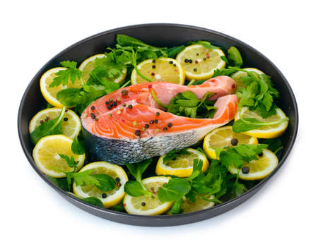 Red fish with lemon, parsley and pepper on plate isolated on white  photo