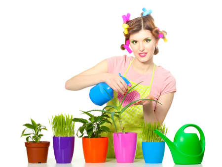 beautiful happy young housewife sprays plants in flowerpots isolated on white Stock Photo - 13446794