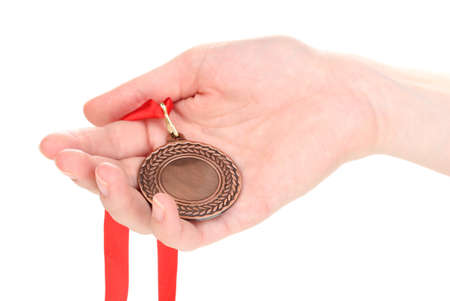 Bronze medal in hand isolated on white Stock Photo - 13275840
