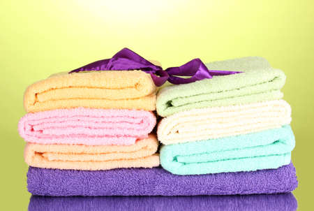 Colorful towels with ribbon on green background Stock Photo - 13275414