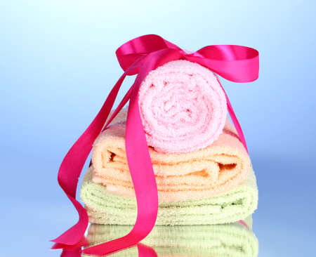 Colorful towels with ribbon on blue background Stock Photo - 13275489
