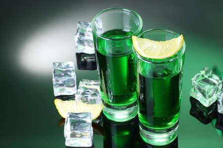 Deux verres d'absinthe, de citron et de glace sur fond vert Banque d'images - 13275384