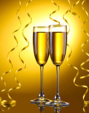 glasses of champagne and streamer on yellow background Stock Photo - 13275533