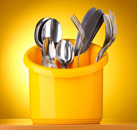 Kitchen cutlery, knives, forks and spoons in yellow stand on yellow background photo