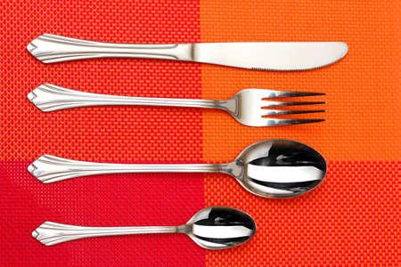 cubiertos de plata: Tenedor, cuchara y cuchillo en una tela roja