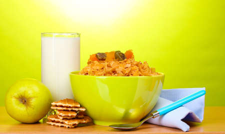 tasty cornflakes in green bowl, apple and glass of milk on wooden table on green background photo