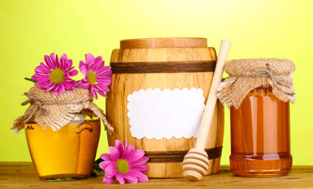 Sweet honey in jars and barrel with drizzler on wooden table on green background Stock Photo - 13304222