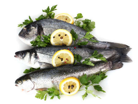 Fresh fishes with lemon, parsley and spice isolated on white photo