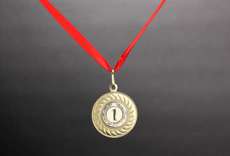 Gold medal on grey background Stock Photo - 13304304