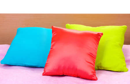 bright pillows on bed on white background photo