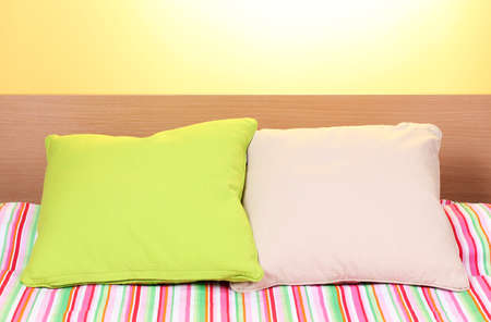bright pillows on bed on yellow background photo