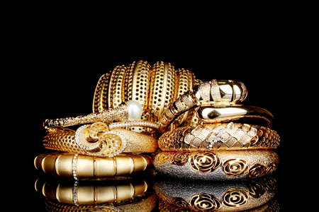 Beautiful golden bracelets isolated on black background Stock Photo - 13304205