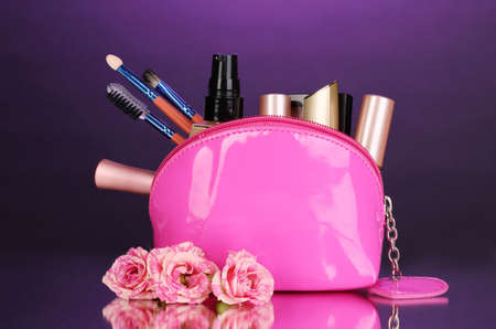Make up bag with cosmetics and brushes on violet background photo