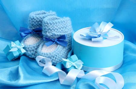 beautiful gifts and baby's bootees on blue silk Stock Photo - 13304209