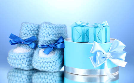 beautiful gifts and baby's bootees on blue background Stock Photo - 13304302