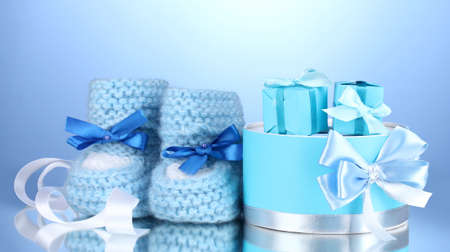 beautiful gifts and baby's bootees on blue background Stock Photo - 13304285