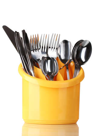 Kitchen cutlery, knives, forks and spoons in yellow stand isolated on white