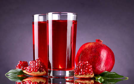 ripe pomergranate and glasses of juice on purple background photo