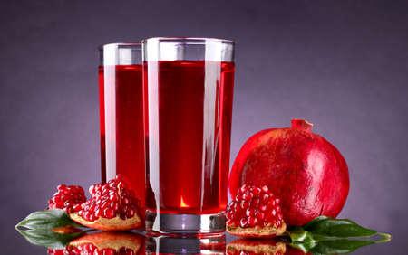 pomergranate: ripe pomergranate and glasses of juice on purple background Stock Photo