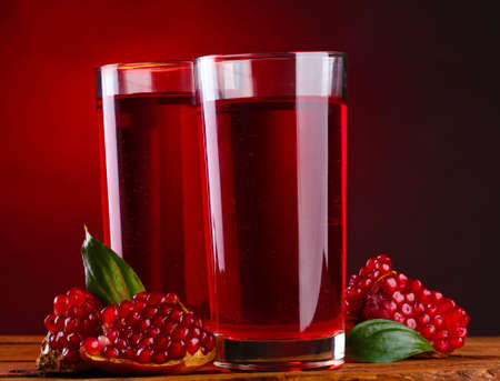 pomergranate: ripe pomergranate and glasses of juice on wooden table on red background Stock Photo