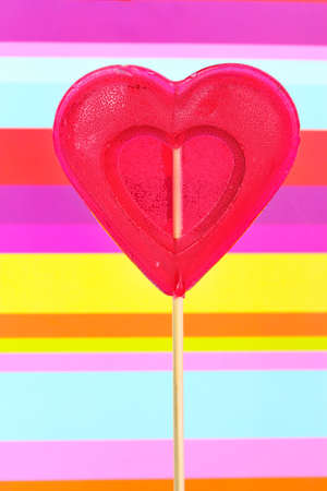 red heart-lollipop on striped background photo