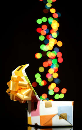 open gift box with bokeh background on black photo