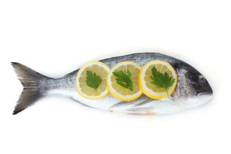 Fresh fish with lemon and parsley isolated on white  photo
