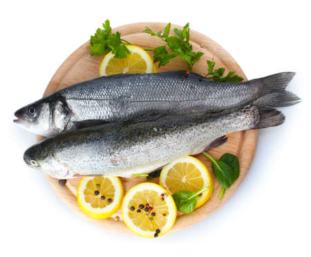 Fresh fishes with lemon, parsley and spice on wooden cutting board isolated on white Stock Photo - 13356109