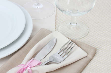 Table setting with fork, knife, plates, and napkin photo