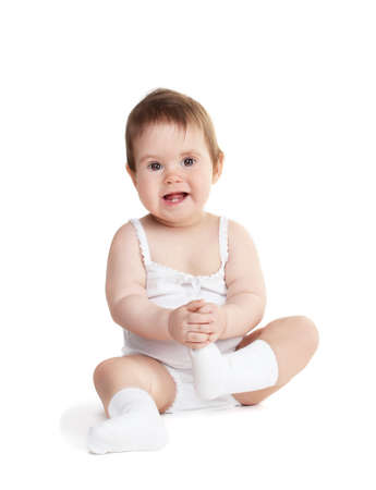 Cute baby girl sitting isolated on white photo