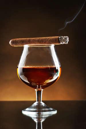 scotch: glas cognac en sigaar op bruine achtergrond