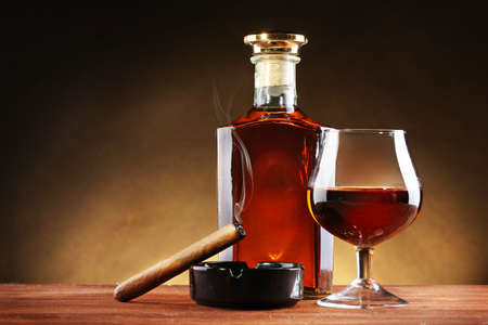 bottle and glass of brandy and cigar on wooden table on brown background photo