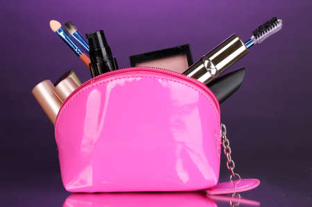 Make up bag with cosmetics and brushes on violet background Stock Photo - 13356060