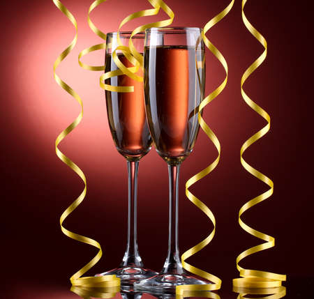glasses of champagne and streamer on red background photo