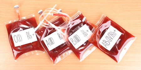 Bags of blood and infusion on wooden background photo