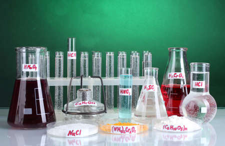 Test-tubes with various acids and chemicals  on bright background photo