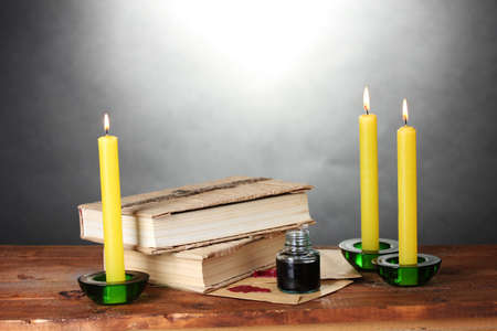 old books, scrolls, ink pen inkwell and candles on wooden table on grey background photo