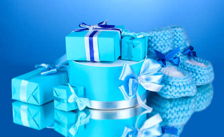 beautiful gifts and baby's bootees on blue background Stock Photo - 13370244