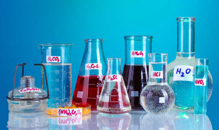 Test-tubes with various acids and chemicals on blue background Stock Photo - 13370248