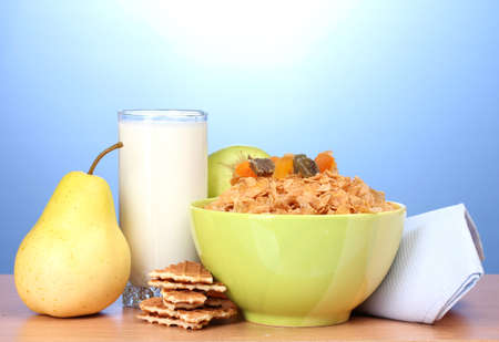 tasty cornflakes in green bowl and glass of milk on wooden table on blue background Stock Photo - 13437935