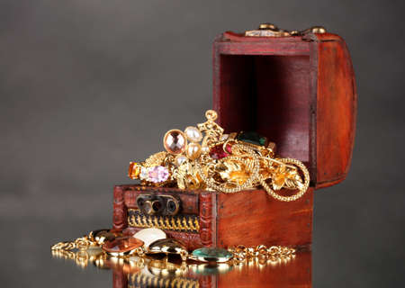 jewellery box: Wooden chest full of gold jewelry on gray background