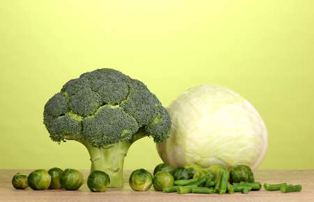 Fresh broccoli and cabbages on wooden table on green background Stock Photo - 13438044