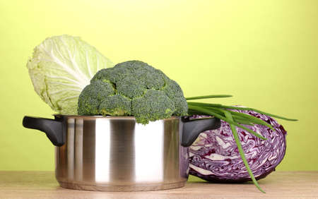 Saucepan with broccoli and cabbages on wooden table on green background photo
