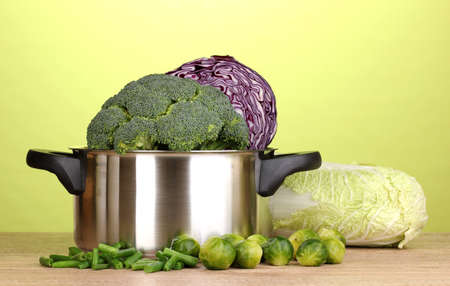 Saucepan with cabbages and broccoli on wooden table on green background photo