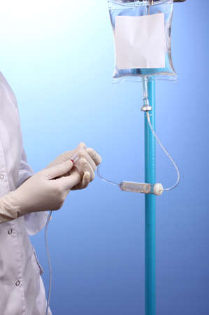 Nurse doing infusion on blue background Stock Photo - 13437940