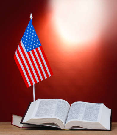 American flag on the stand and books on wooden table on red background photo